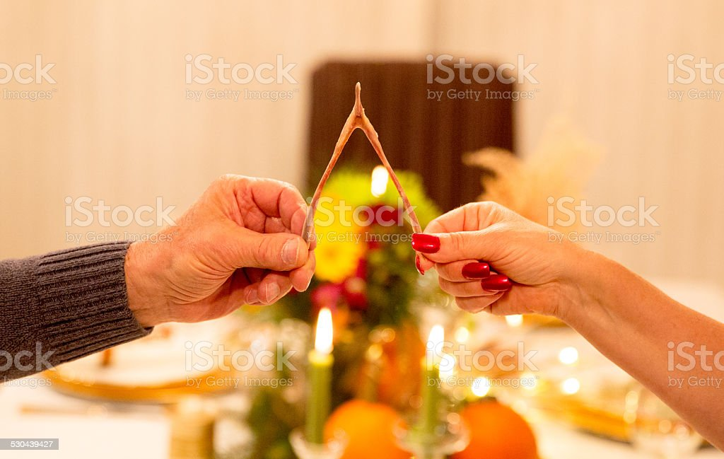 Wishing You Happy Holidays: Two people pull on wishbone stock photo