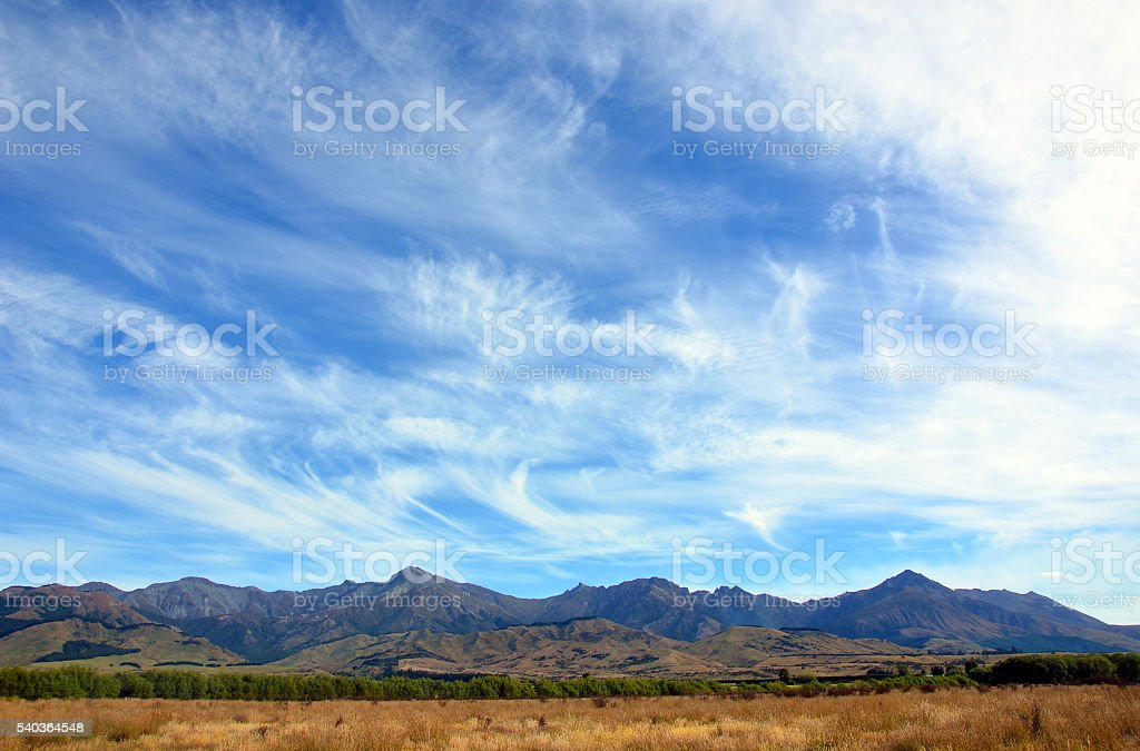 Wispy clouds in blue skies above a rugged mountain range stock photo