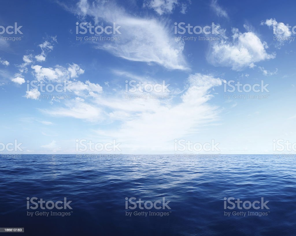 Wispy Clouds over Deep Blue Ocean stock photo