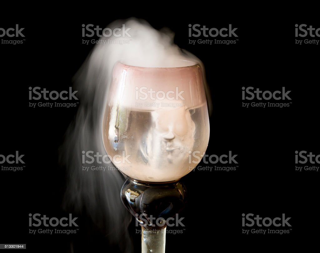 wispy smoke from wine glass stock photo
