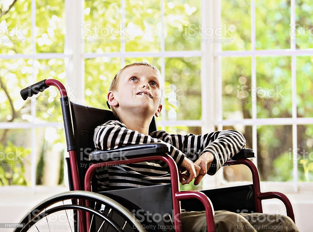 Wistful boy in wheelchair looks up longingly stock photo