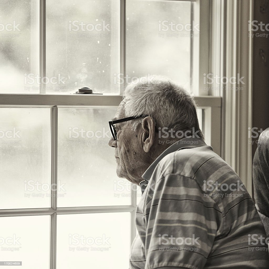 Wistful Senior Man Looking Through Grungy Window stock photo