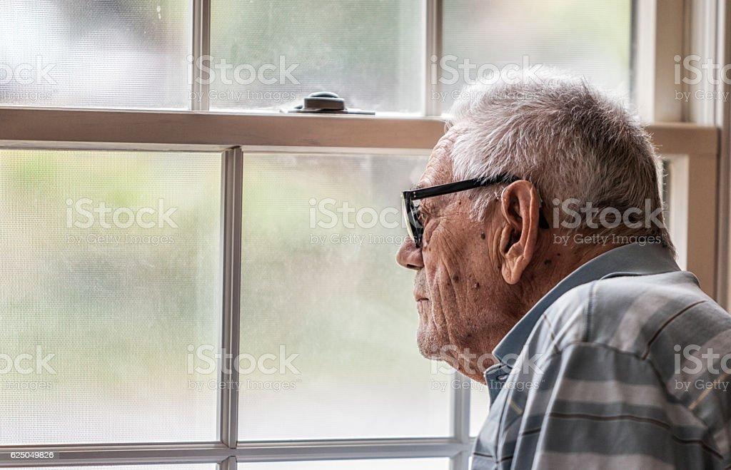Wistful Senior Man Staring Through Hazy Window stock photo