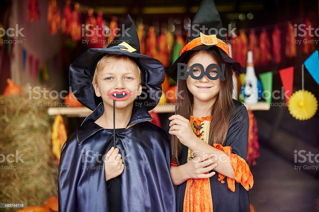 Witch and wizard in scary masks on stock photo