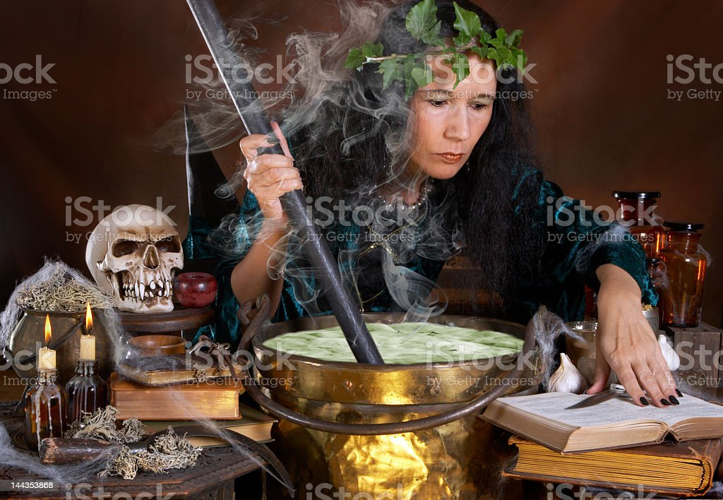 A witch brewing a green potion with cobwebs stock photo