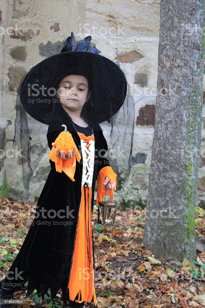 Witch child with a pumpkin in Halloween eve stock photo
