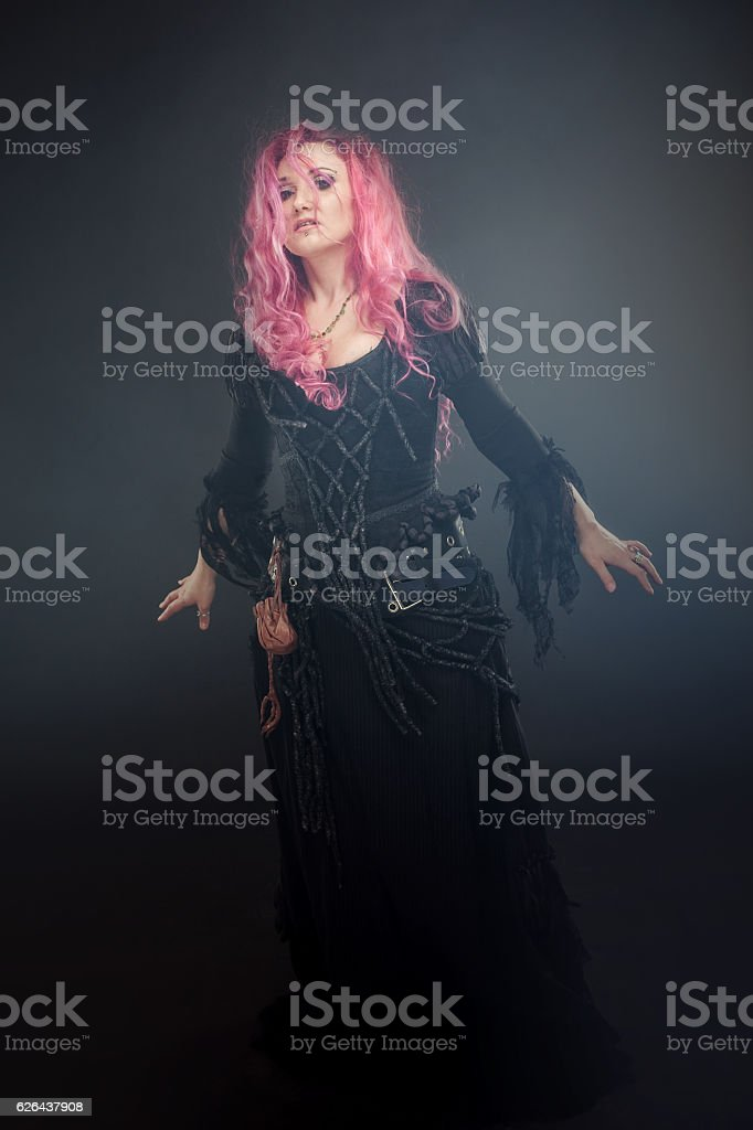Witch creates magic. Attractive woman with red hair in witches stock photo