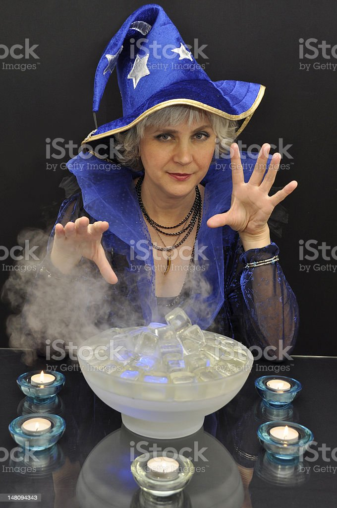 Witch in blue hat with magic crystals and candles stock photo
