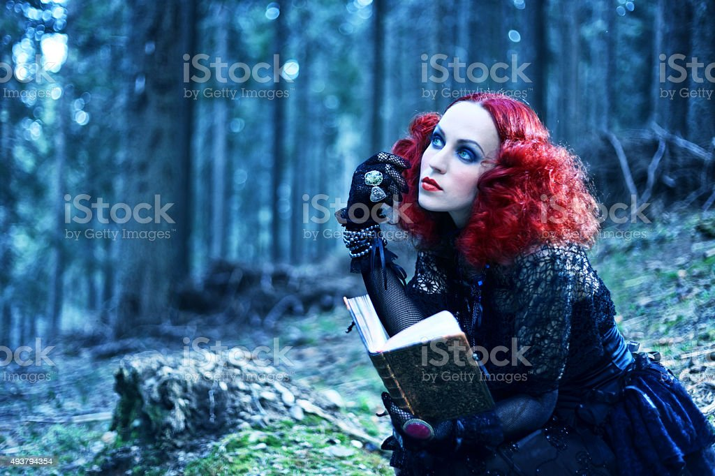 Witch in the forest rading book. Halloween theme stock photo