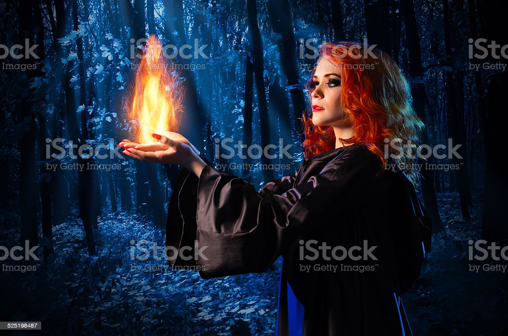 Witch in the night forest holds fire stock photo