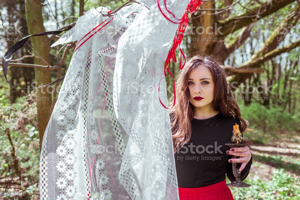 witch in the woods with a candle stock photo