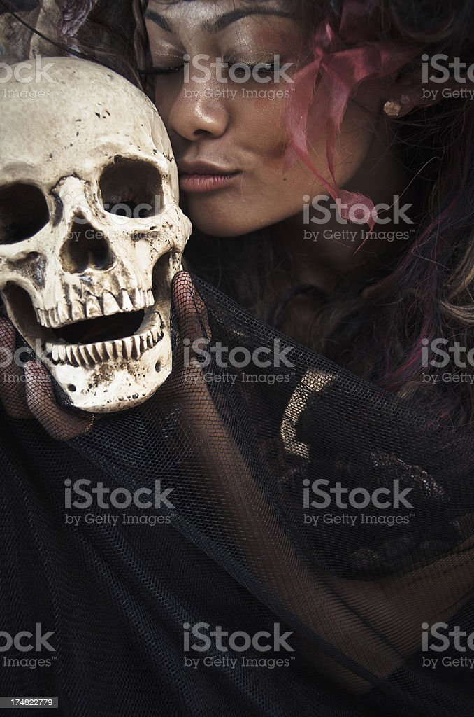 Witch Kissing a Human Skull royalty-free stock photo