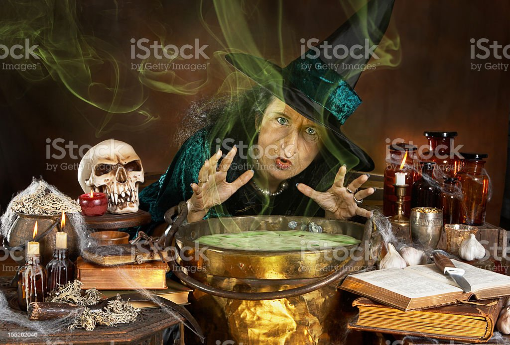 Witch making a potion in her pot royalty-free stock photo