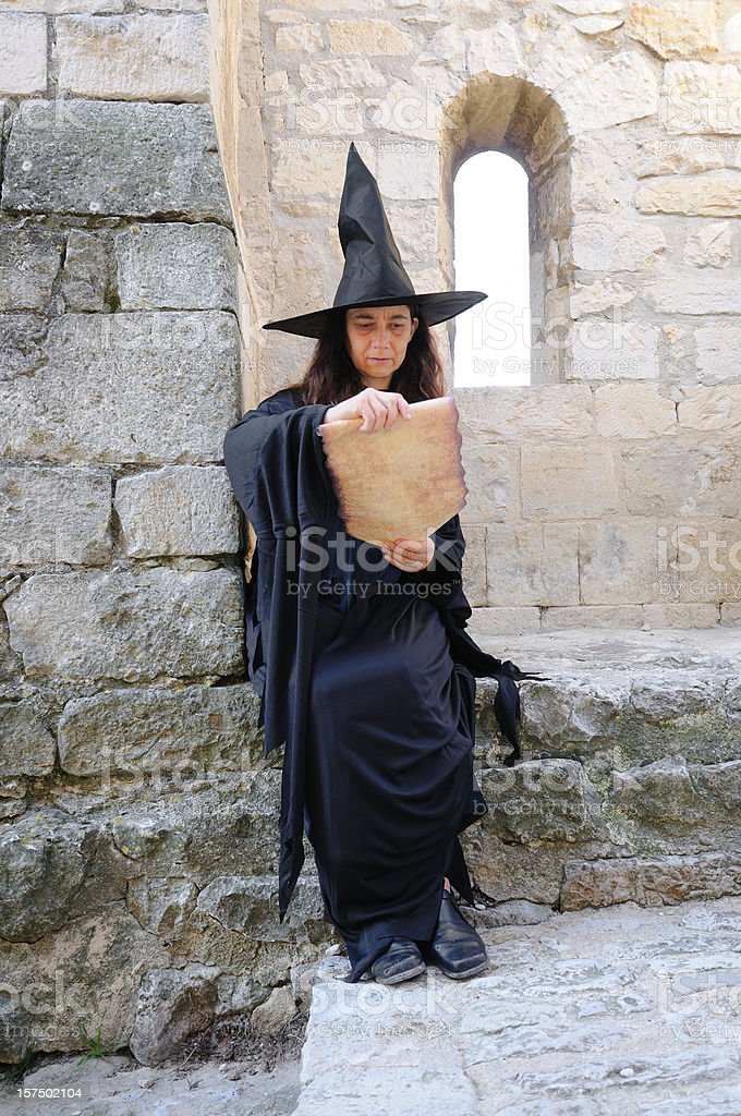 witch reading scroll stock photo