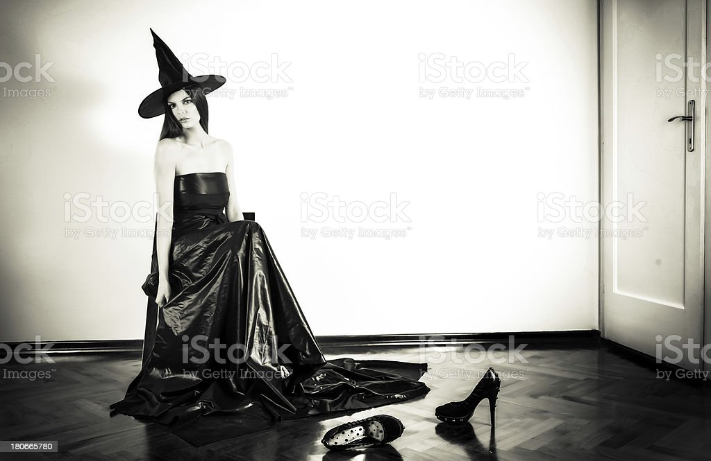 witch sitting on chair in room black and white royalty-free stock photo