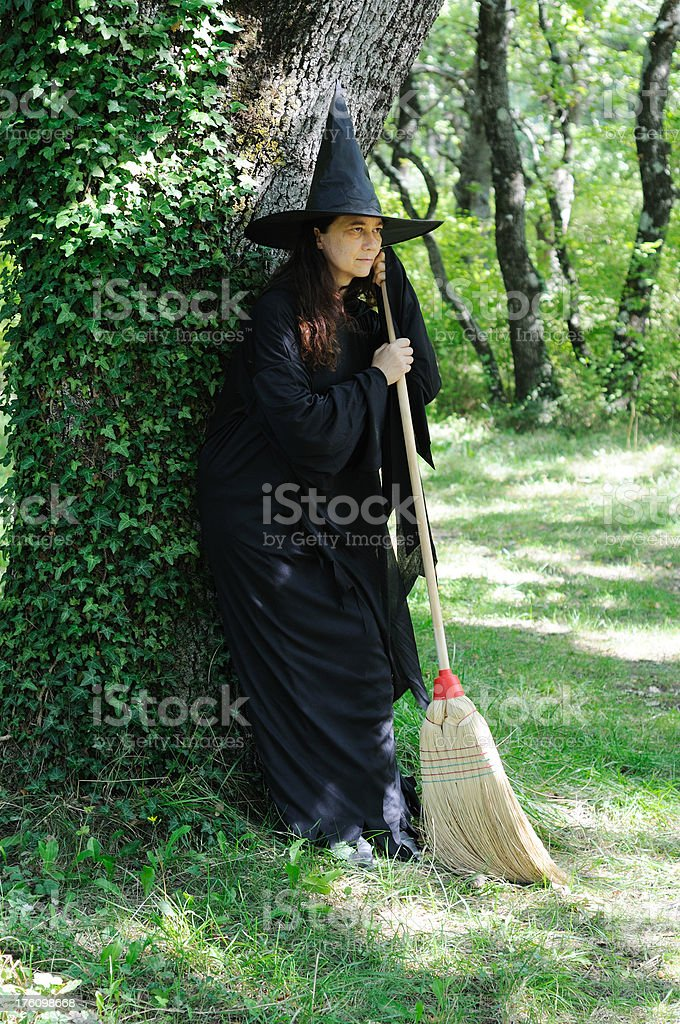 Witch standing against tree stock photo