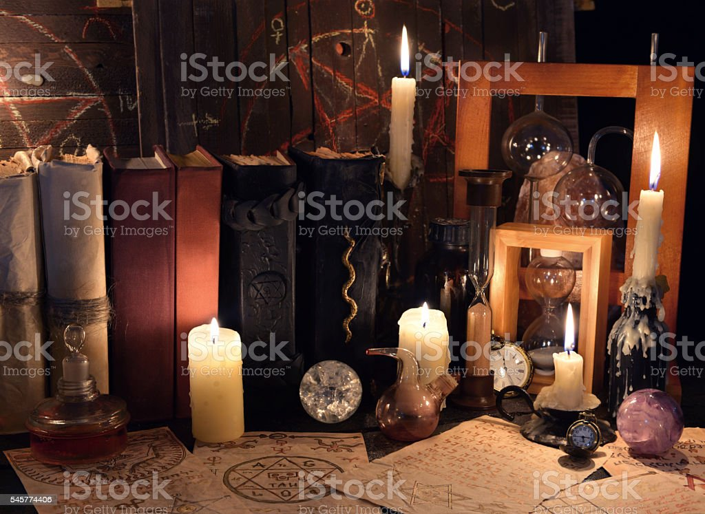 Witch table with magic objects, candles and old mystic parchments stock photo