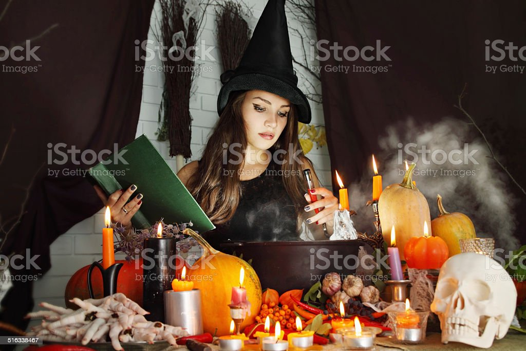 witch with a book and a test tube of blood stock photo