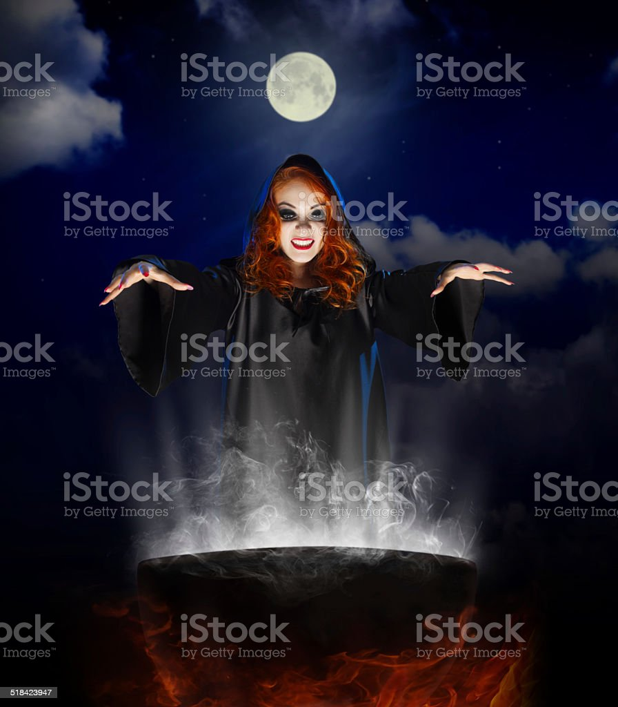Witch with cauldron on night sky background stock photo