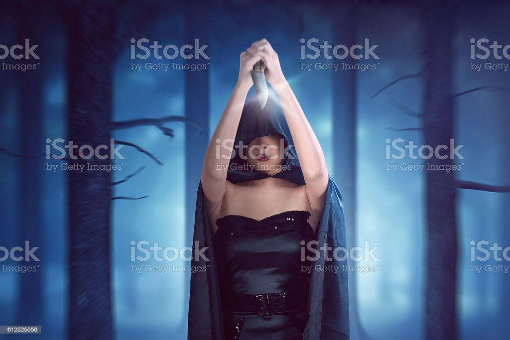 Witch woman with black cloak has knife held high and stock photo