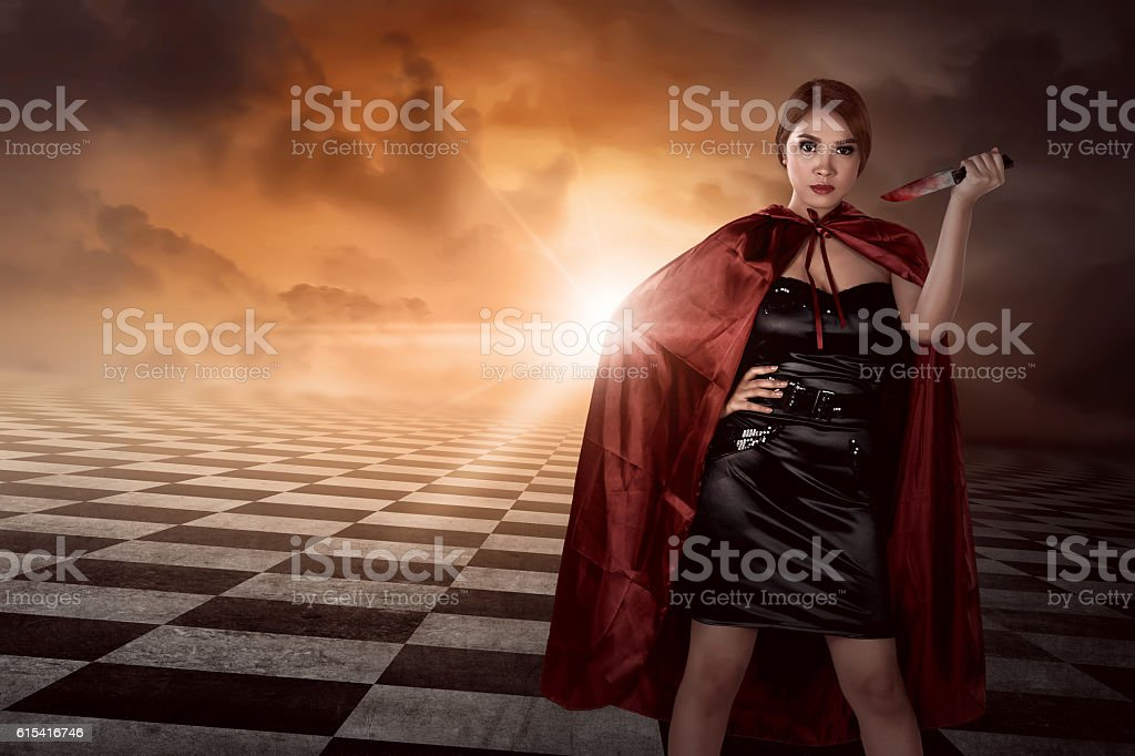 Witch woman with black costume wearing cloak hold knife stock photo