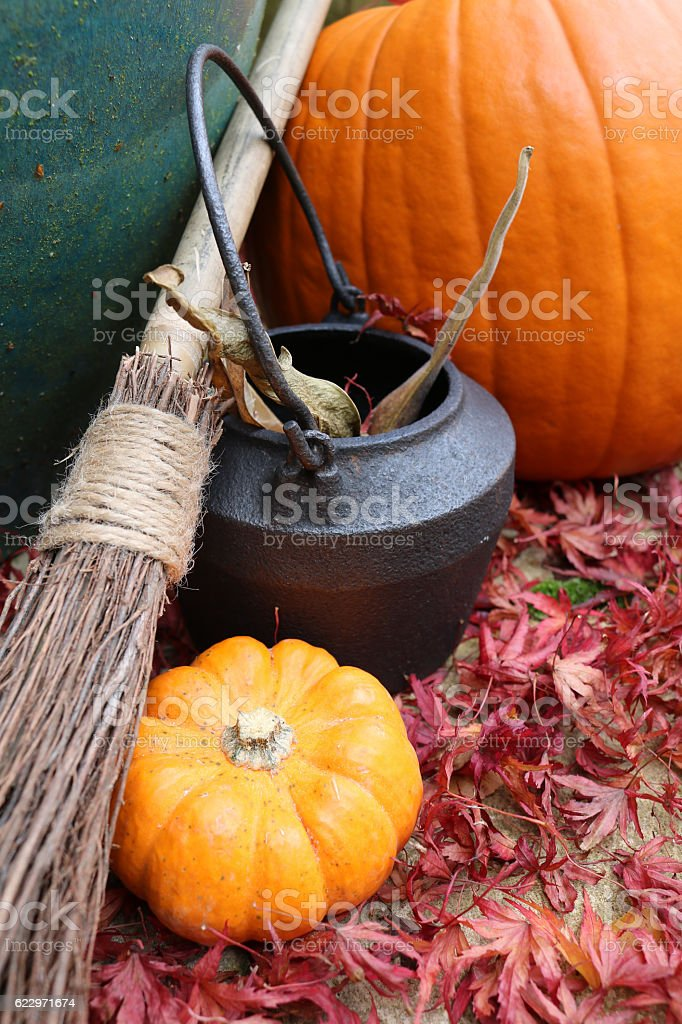Witches starter kit of broomstick, cauldron and pumpkins stock photo