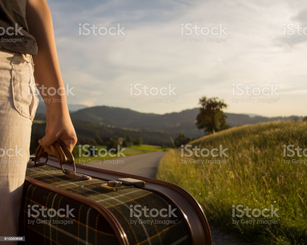 With a suitcase on the road stock photo