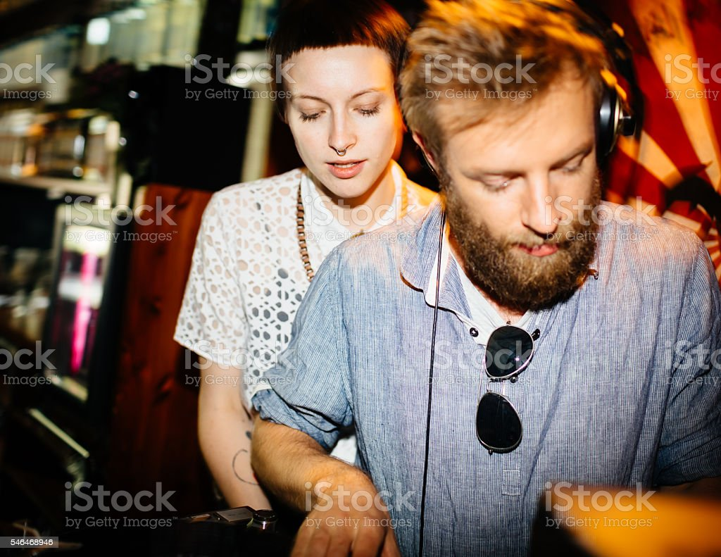 DJ with Groupie in background stock photo