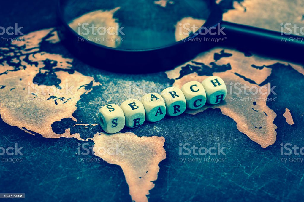 SEARCH with magnifying glass on grunge world map stock photo