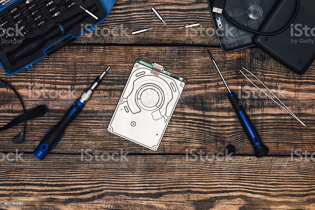 HDD with Precision Screwdriver on Wooden Table stock photo