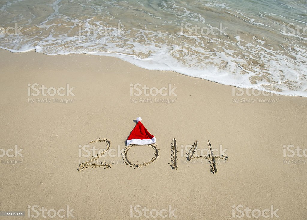 2014 with santa hat on sea beach sand royalty-free stock photo