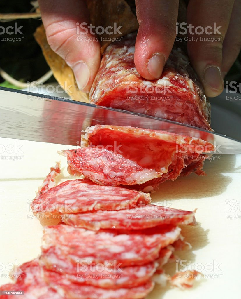 SALAMI with steel knife that cuts 4 royalty-free stock photo