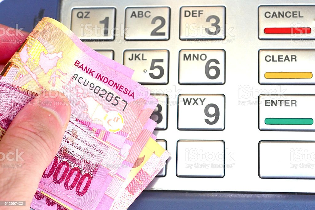 Withdrawing Indonesian Rupiah from an ATM stock photo