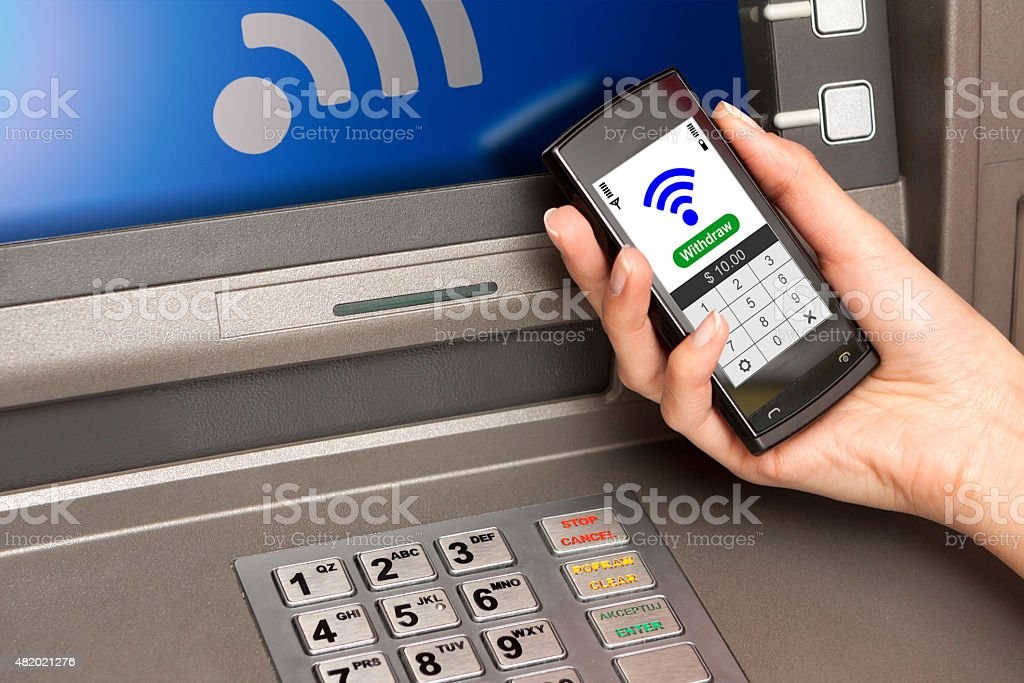 withdrawing money atm with mobile phone (NFC near field communic stock photo