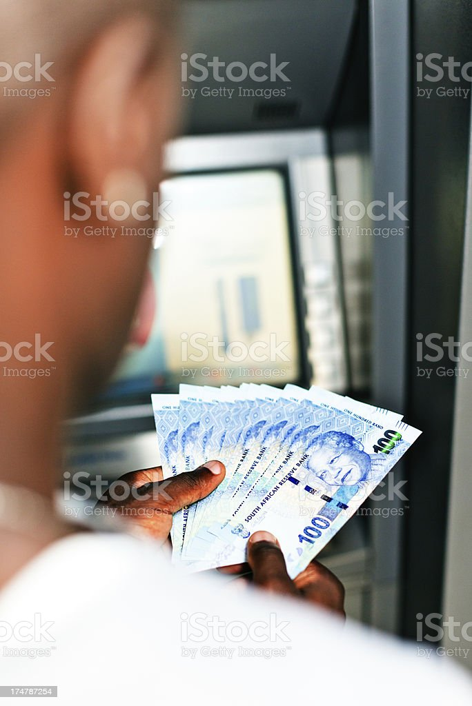 Withdrawing new South African Hundred Rand notes from an ATM stock photo
