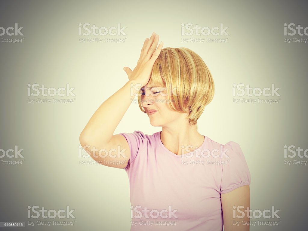 Witless young woman holding her hand to her forehead stock photo