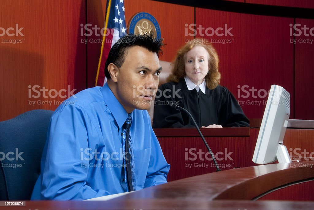 Witness testifying at the stand in federal court, judge watching stock photo