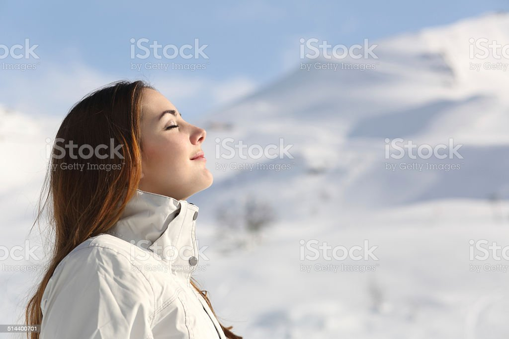 Wman breathing fresh air in winter in a snowy mountain stock photo