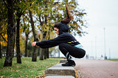 Wman outdoor at park doing fitness exercise jumps.