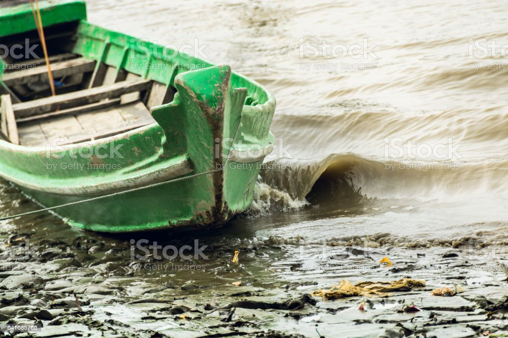 Wobbling boat attached to tidal riverbank stock photo