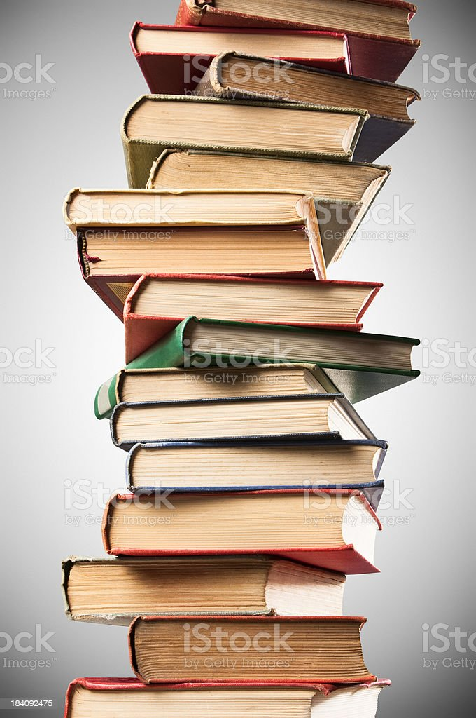 Wobbly stacks of old leather bound books on grey background royalty-free stock photo