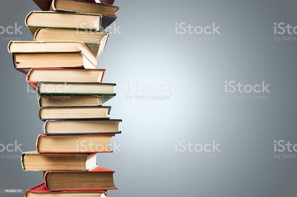 Wobbly stacks of old leather bound books with copy space royalty-free stock photo