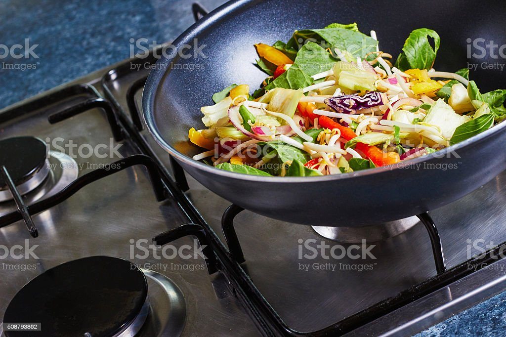Wok on a stove with stir fry vegetables stock photo