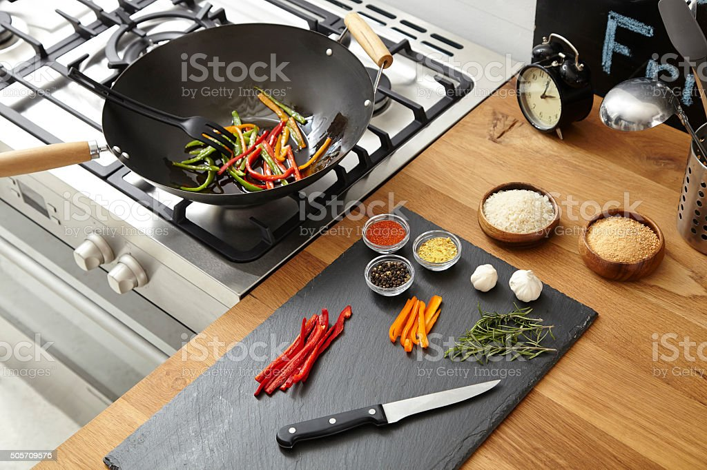Wok on the stove, fresh vegetables on the table stock photo