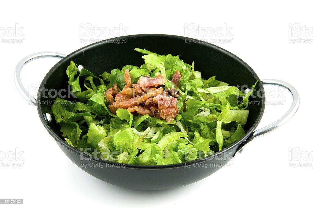 Wok pan with endive and bacon royalty-free stock photo