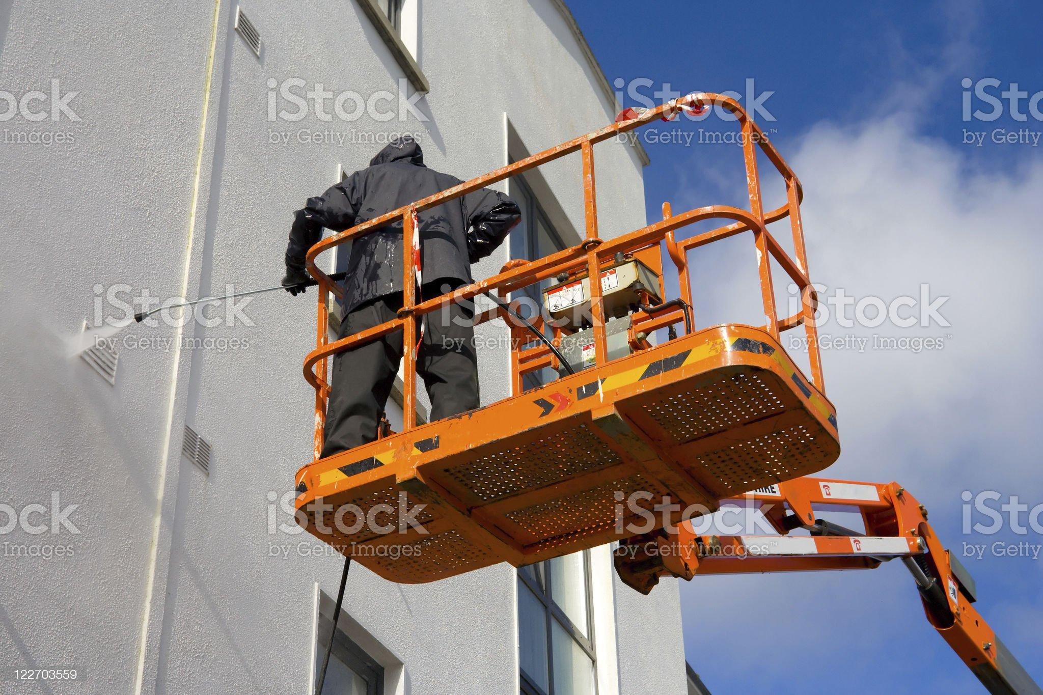 woker in platform washing a building royalty-free stock photo
