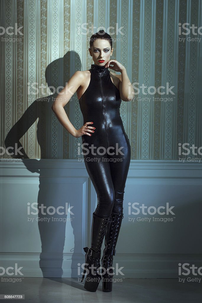 Womam in catsuit posing at vintage wall royalty-free stock photo