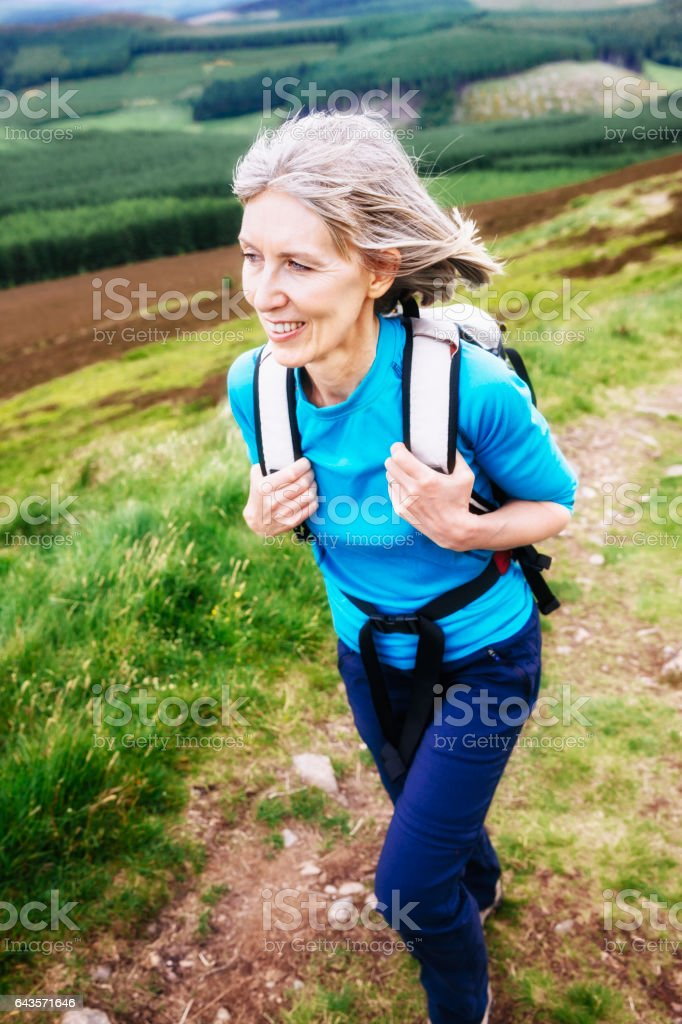 Woman 50-59 years, hiking with backpack stock photo