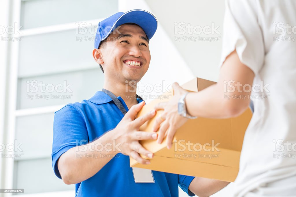 Woman accepting a delivery of cardboard boxes from deliveryman stock photo