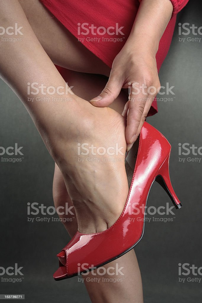 woman aching feet red heels over grey royalty-free stock photo